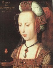 Mary of Burgundy wears a headdress comprising a truncated-cone hennin, a jewelled padded roll (bourrelet), and a sheer veil.