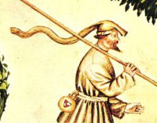 Man walking in a brisk wind wears a chaperon that has been caught by a gust. He wears a belt pouch and carries a walking stick, late 1300's