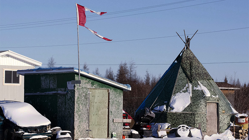 The remains of a Canadian flag can be seen flying over a building in Attawapiskat, Ont. on November 29, 2011. (Adrian Wyld/CP)