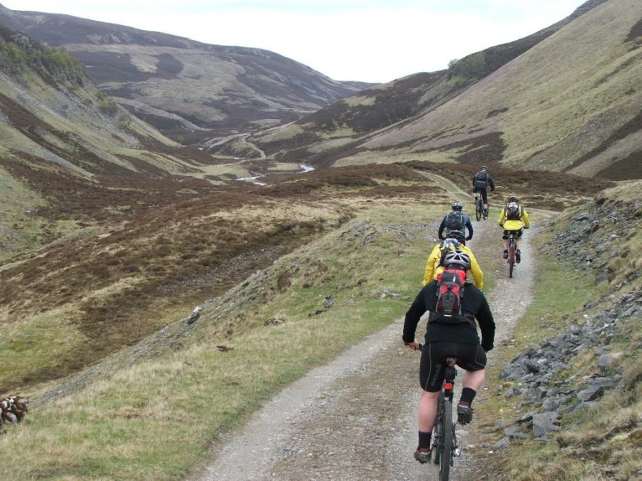 Mountain bikers speed down a hill in rural Scotland