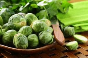 whole brussel sprouts in a brown bowl next to cut brussel sprouts and a green napkin