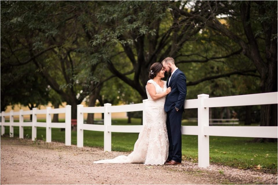 Bride and groom embracing by white fence on wedding day. Maddie Peschong Photography.