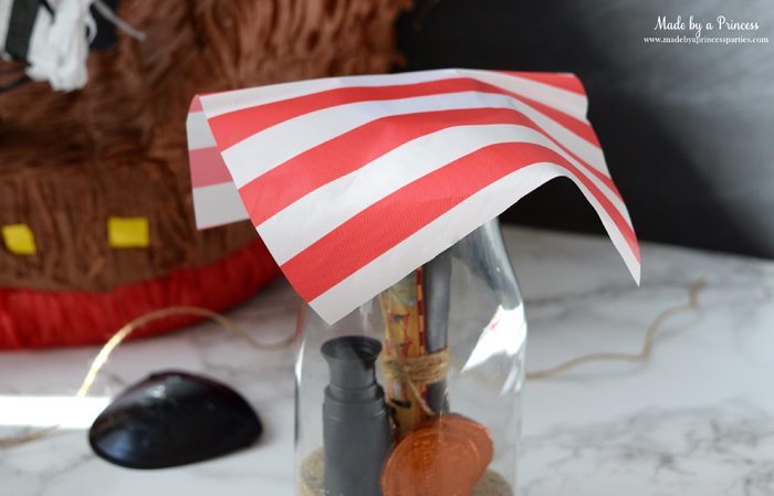 Pirate Bottle Invitations Party Idea place piece of plastic tablecloth on glass milk bottle