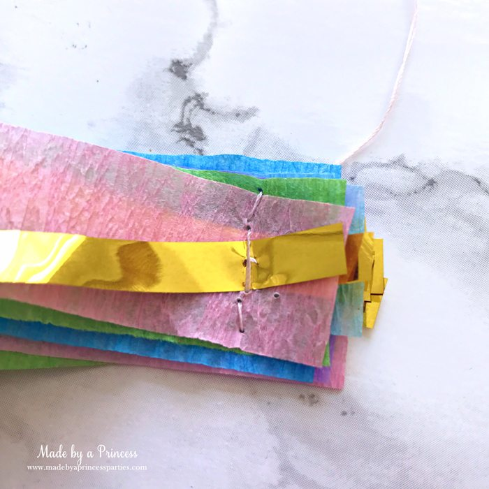 unicorn princess party hat idea tutorial layer crepe paper and gold fringe bring threaded needle through all layers and sew together