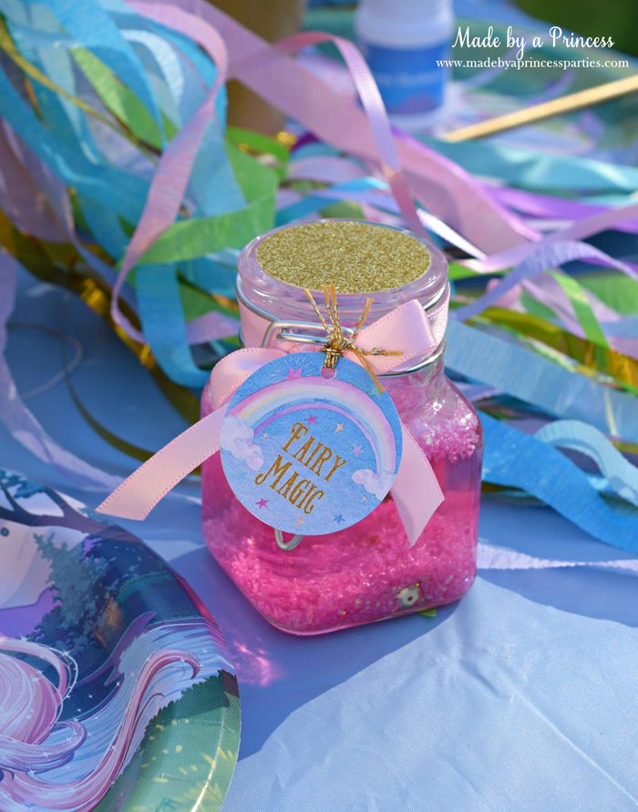 Glitter Fairy Jar Party Idea Tutorial filled with sequins and tied with a pretty ribbon and custom tag