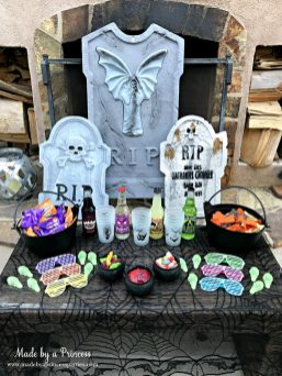 Teen Halloween Party Ideas simple table of snacks drinks and treats use tombstones as backdrop Made by a Princess #halloweenparty #teenhalloween
