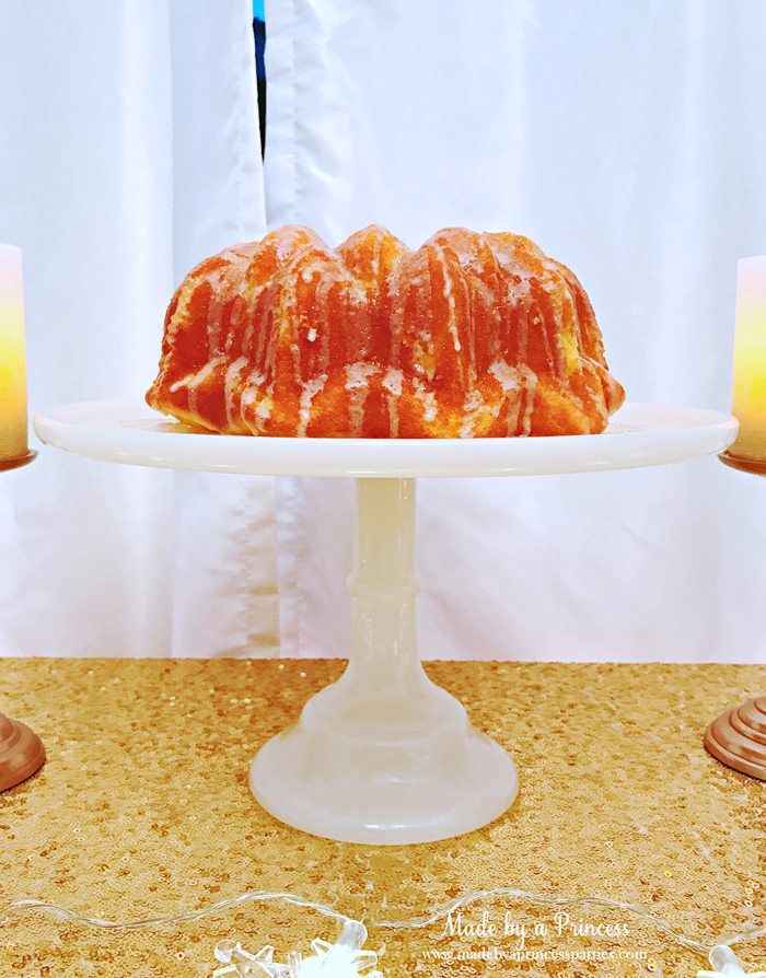 Champagne Poke Cake with Champagne Glitter Glaze on Cake Stand