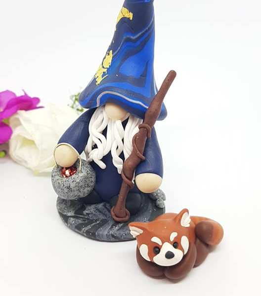 Clay wizard gnome in blue and gold from Made By Me Crafts with bucket of magic sparkles next to a red panda