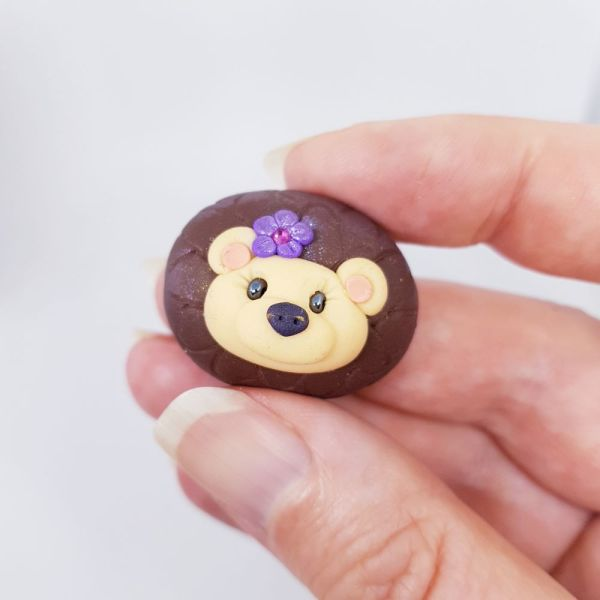 hand holding small brown pebble shape with hedgehog face and purple flower