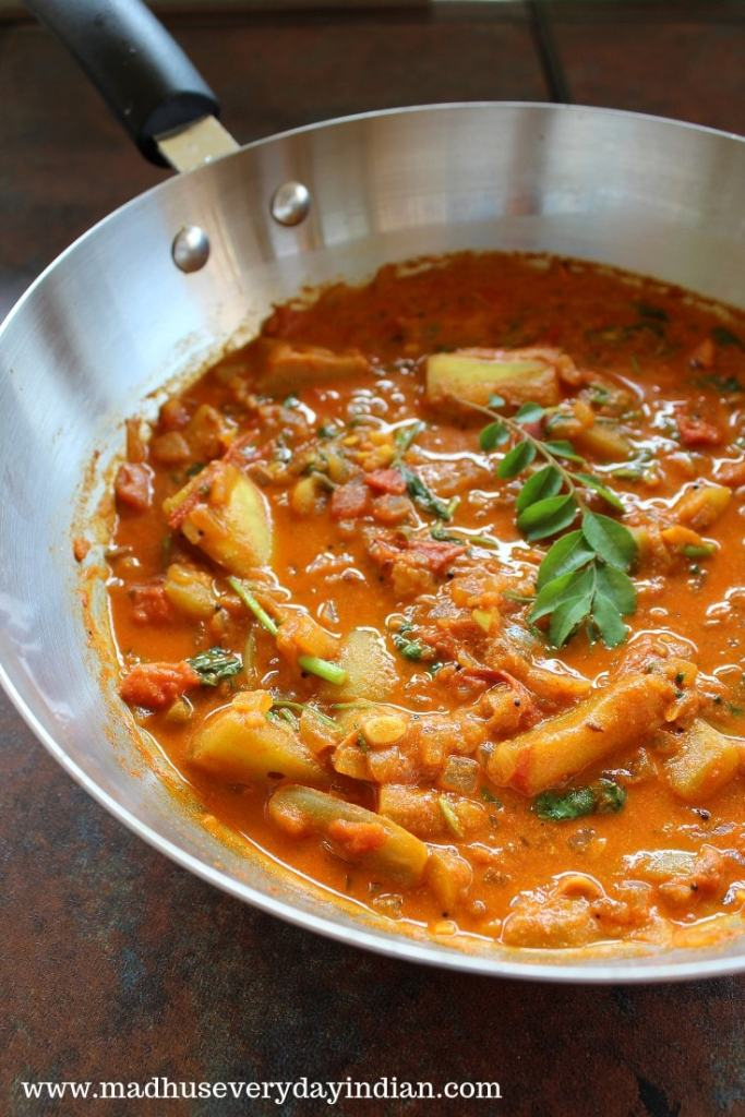 bottle gourd curry topped with curry leaves in a steel pan