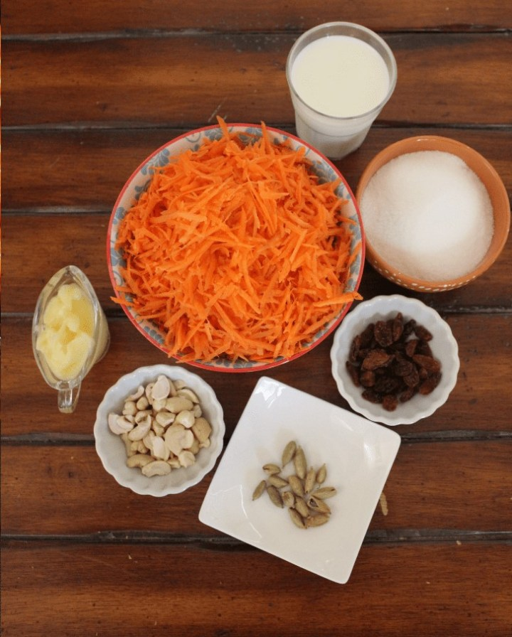 carrot halwa ingredients- grated carrot, milk, milk powder, sugar, ghee, cardamom, cashe, raisins