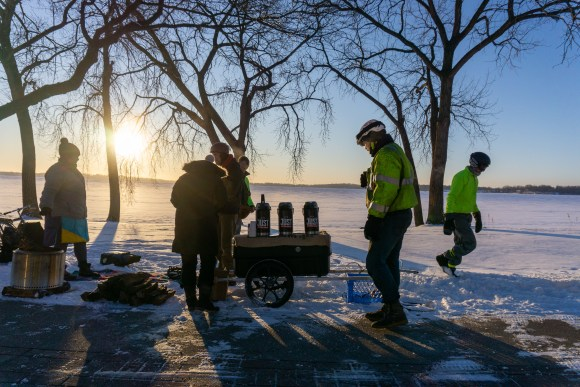A group of people standing around a bike trailer with three coffee urns on it. Frozen Lake Monona and a rising sun in the background.