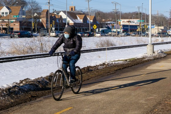 A cyclists wearing a mask near the intersection of University Bay Drive and University Ave/Campus Drive.
