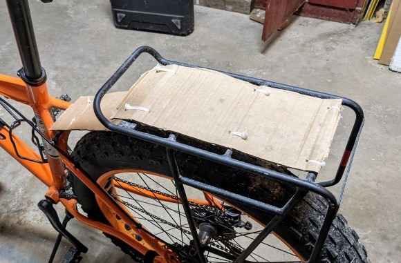 An orange bike with cardboard fenders secured with zip ties.