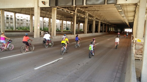 Cyclists riding on all lanes of John Nolen Drive under the Monona Terrace Convention Center
