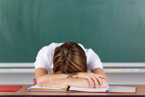 white female teacher head on desk frustruated tired exhausted burnt out