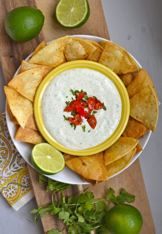 Jalapeno Ranch Dip in a yellow bowl, on a plate with tortilla chips and lime