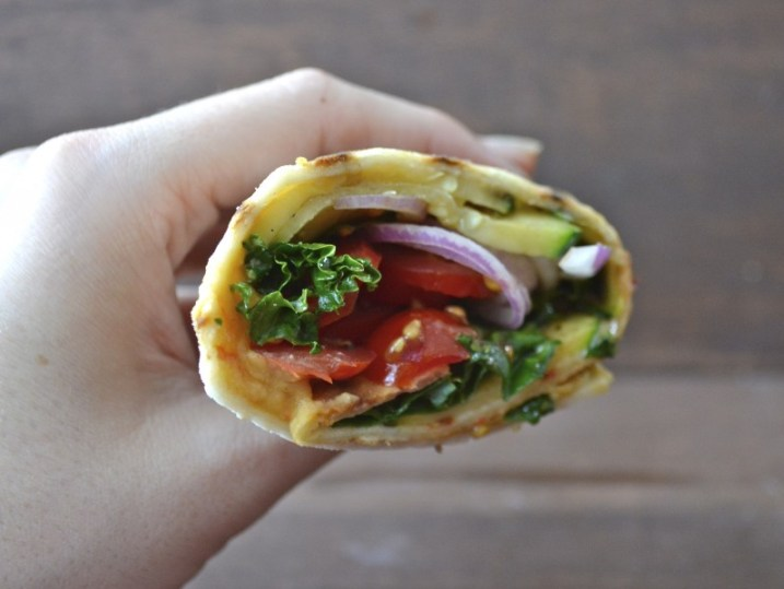 a grilled veggie and hummus wrap being held aloft, seen from the side