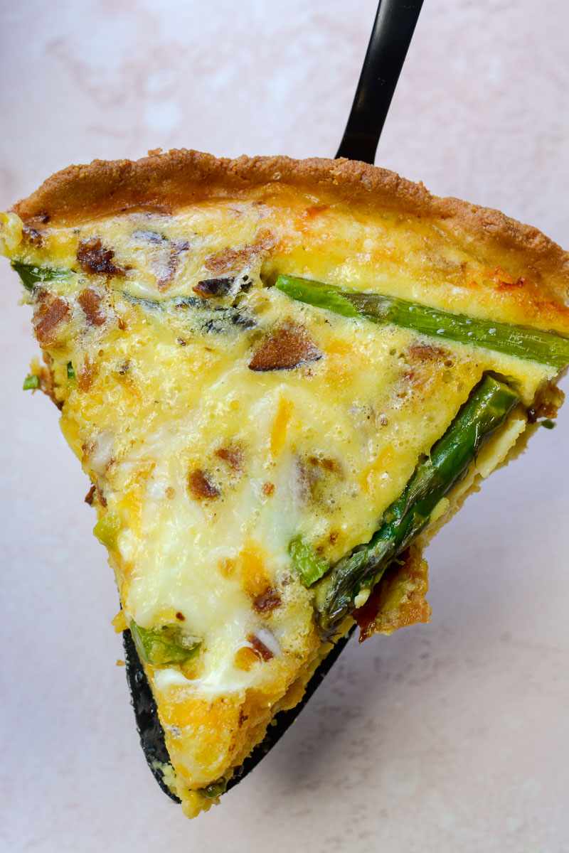 A slice of asparagus, bacon and cheddar quiche.