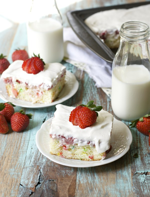 two slices of strawberry poke cake on white plates next to two glass jugs of milk.