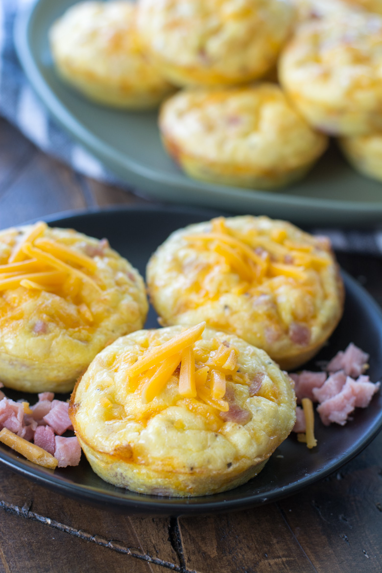 three ham and cheese keto egg muffins on a gray plate. More egg muffins rest in the background.