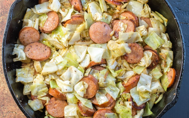 Need an easy low carb, one pan dinner? I've got you covered! This Keto Sausage and Cabbage Skillet is ready in under 20 minutes and has less than 6 carbs per serving! #keto