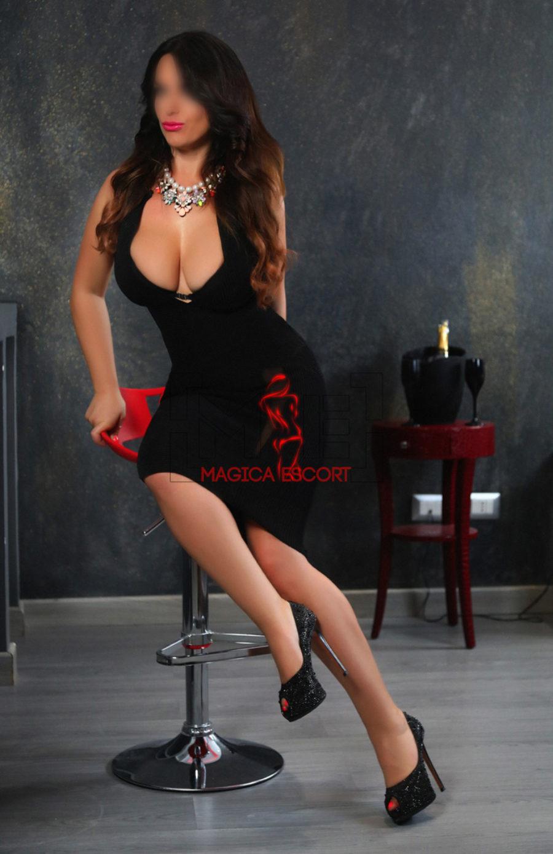 Alina escort Milano seduta sullo sgabello con uno splendido abito da sera nero.