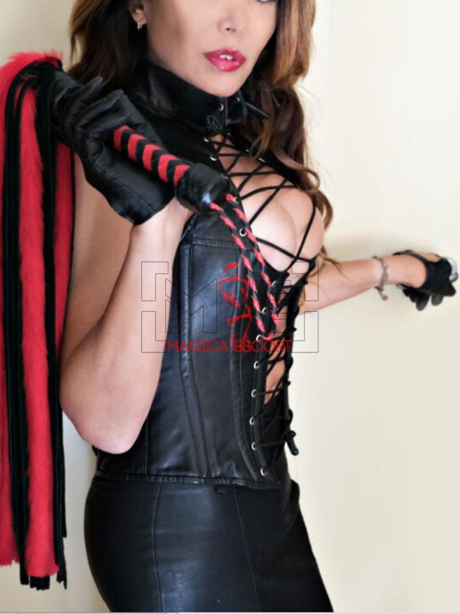 Sabrina escort Genova fotografata con la frusta per domare i suoi fedeli schiavi adulanti