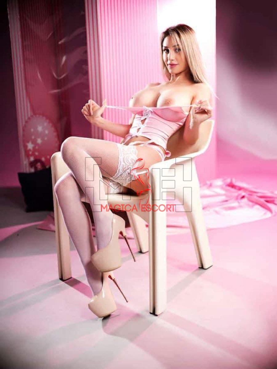 Cleo escort ungherese è seduta sulla sedia e indossa un completino intimo color rosa pastello davvero splendido.
