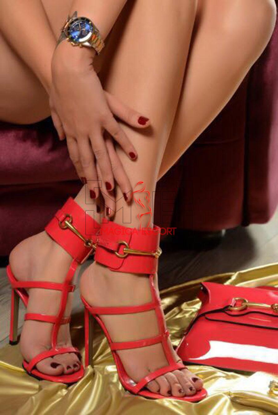 Marisol escort Bolzano esibisce i bellissimi piedi che indossano un meraviglioso paio di sandali di colore rosso.
