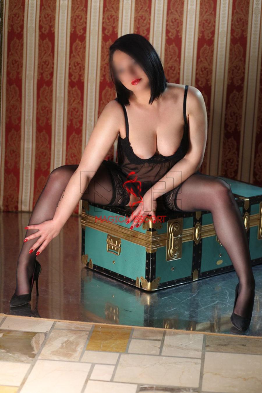 Escort girl Vittoria indossa un body nero che lascia intravedere il seno genoroso ed abbondante. Magica Escort.