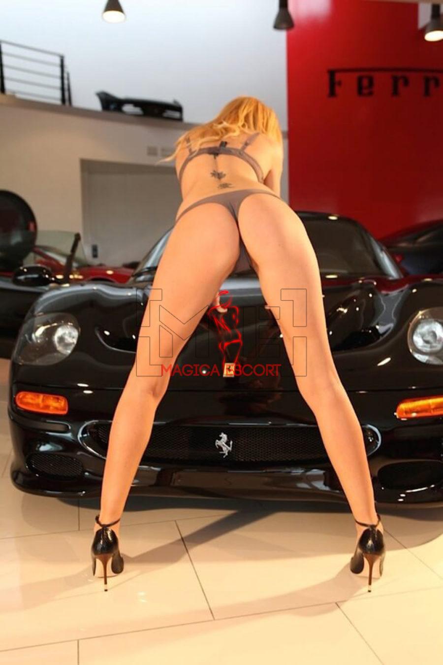 Mademoiselle Sofia top escort Brescia in posa erotica appoggiata ad una Ferrari nera.
