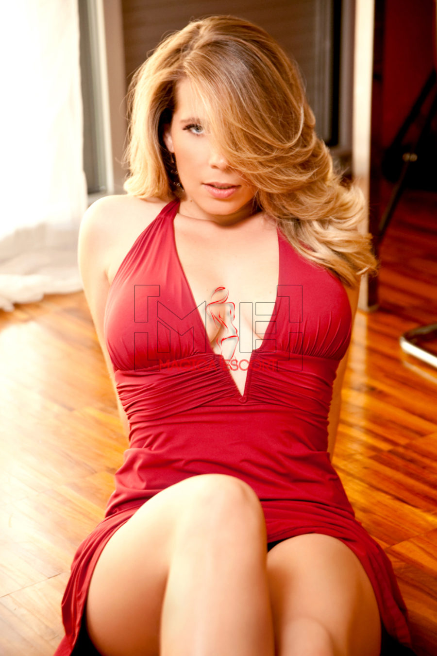 Cherry top class escort Torino indossa un abito rosso dalla profonda scollatura.
