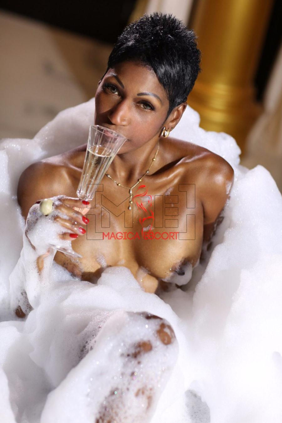 Escort cubana Sharon avvolta nella schiuma mentre beve dello champagne nella sua vasca da bagno. Magica Escort.
