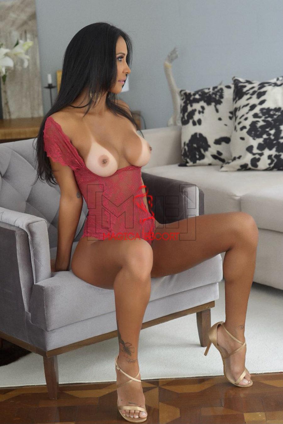 Carmela brasiliana top class Roma fotografata a seno nudo nella poltrona di casa. Magica Escort