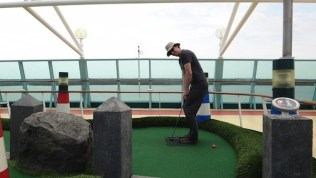 Andrew Playing Mini Golf With The Ocean Behind Him