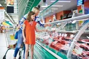 43959022 - mother and daughter chooses a meat in the supermarket