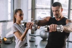 Personal trainer com aluno no treino de musculação