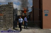 Garda Ronan Coleman and Jerome Hartnett await the arrival of the fire brigade at the rear of the historic building on the corner of Limerick Road / Main Street this afternoon. ©Photograph: John Reidy