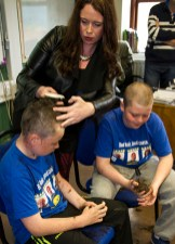 Just minutes in and hairdresser, Christina is onto Conor's head already leaving Luke with a fistful of his own hair during their Shave or Dye performance at Gaelscoil Aogáin on Friday. ©Photograph: John Reidy