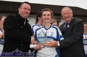 Desmonds centre-back Cáit Lynch receiving the TESCO Player-of the-Match award from President of the Ladies Gaelic Football Association, Pat Quill (right) with Paul O'Loughlin of TESCO after the final in Corofin, Co. Clare in November 2014. ©Photograph: John Reidy 29-11-2014