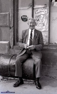 Gene McGillicuddy watching Castleisland's first St. Patrick's Day Parade from the 'Hogan Stand.' The tar barrell he sat on was outside Hogan's / Wren's for years and was polished by the generations of locals who used it as a meeting place. ©Photograph: John Reidy 17-3-1989