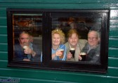Home and dry and wetting the whistle: Members of the Brennan's Bar delegation in Day's Bar on Inishbofin soon after arrival. Con 'Rocky' Roche (left) with the partly hidden Eamon Fleming, Cathleen Reidy, Mike Kenny RIP and Seán Brennan, RIP. Photograph: John Reidy 6-6-2003
