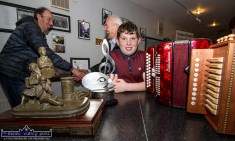 Double All-Ireland champion, Michael Healy gets on with the business of having his photograph taken with his instruments and his trophies while Handed Down founder, Mick Culloty (left) greets John Walsh from Newmarket at the opening night of the 2019 series of Handed Down at Scartaglin Heritage Centre. ©Photograph: John Reidy 19-10-2019