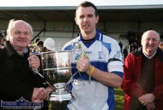 A moment to savour for Castleisland Desmonds GAA Club Chairman, Jimmy Greaney (right) as North Kerry board Chairman, Liam Dennehy presents captain, John Brennan with the Eamon O'Donoghue Memorial Cup after he led his side to victory over Finuge in the North Kerry Senior Football Championship final in Ballylongford in early 2008. ©Photograph: John Reidy 10-2-2008