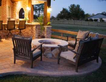 Outdoor Patio Seating Area Prosper TX featuring a professional outdoor design incorporating patio seating area with fire pit and outdoor kitchen in back yard.