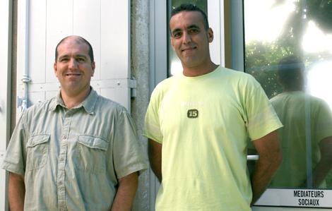 Cette photo représente deux hommes se faisant prendre en photo devant un mur et une fenêtre. Ils se tiennent droit et sourrient