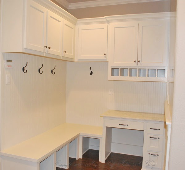 Beadboard mudroom with built in desk and upper cabinets
