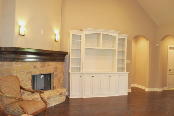 Living room with stone fireplace white built in and wood floors