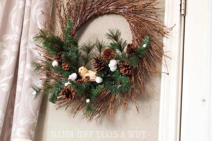 Bird on Evergreens for winter wreath. World Market inspired wreath. A fun twist on a Christmas wreath. Make a winter wreath that will last all season long and well past. This cute grapevine wreath is adorned with a tiny bird, pinecones, greenery and pom poms. You won't believe how cheap and easy this was to make! And so simple! #Christmas #winter #holiday #wreath #nature #knockoff